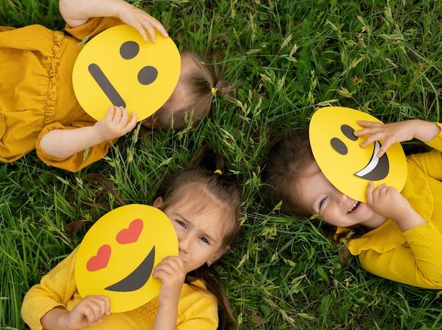 Drie kinderen liggen op het gazon in het gras en bedekken hun gezicht met emoticons