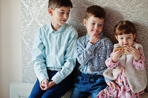 Drie kinderen. meisje met mobiele telefoon bij de hand.