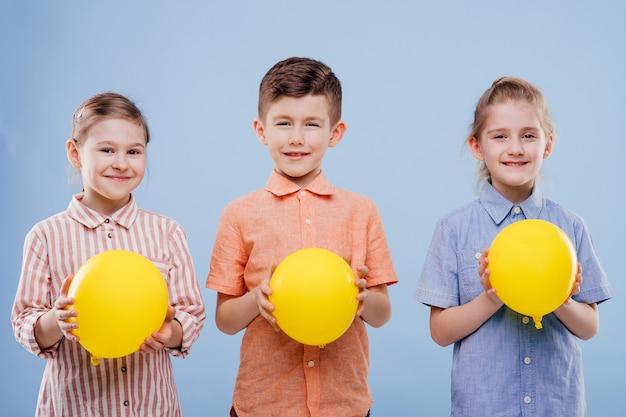 Drie kinderen met gele ballonnen met een glimlach kijken naar de camera geïsoleerd op blauwe achtergrond kopiëren...