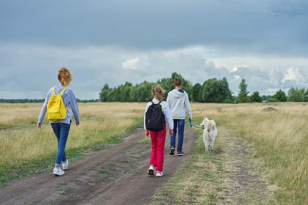 Drie kinderen met hond wandelen langs landweg, uitzicht vanaf de achterkant
