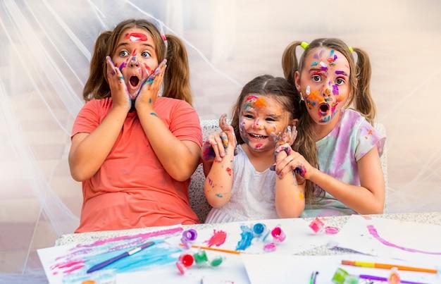 Drie kinderen schilderen met verf. meisjes lachen vrolijk en maken plezier.
