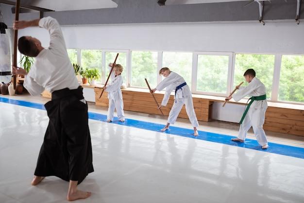 Drie kinderen voelen zich betrokken en geïnteresseerd in het leren van aikido met hun professionele leraar