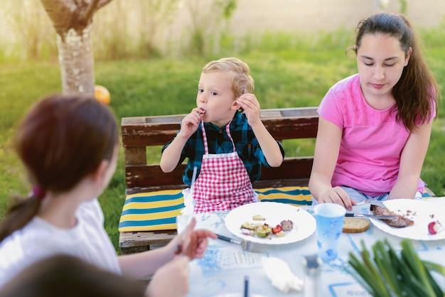 Drie kinderen zitten bij de tafel in de natuur en eten.