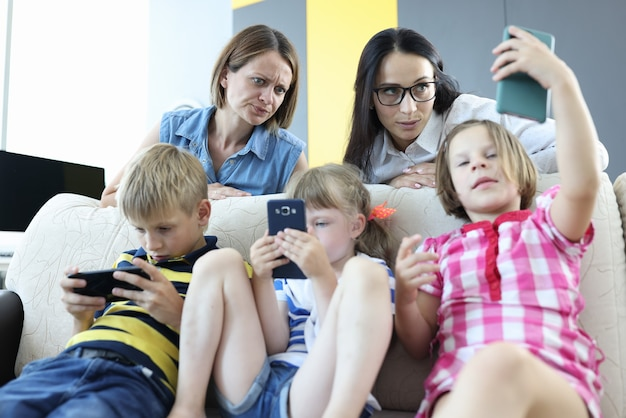 Drie kinderen zitten naast elkaar op de bank en spelen spelletjes op de telefoon. een vrouw kijkt ongelukkig naar het telefoonscherm van de dochter