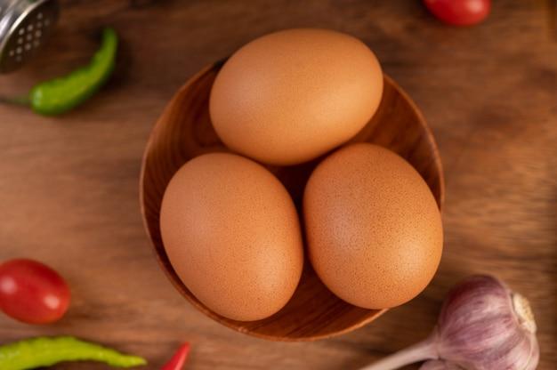 Drie kippeneieren op het bord met knoflook tomaten en chili.