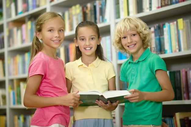 Drie klasgenoten poseren voor de camera in een openbare bibliotheek