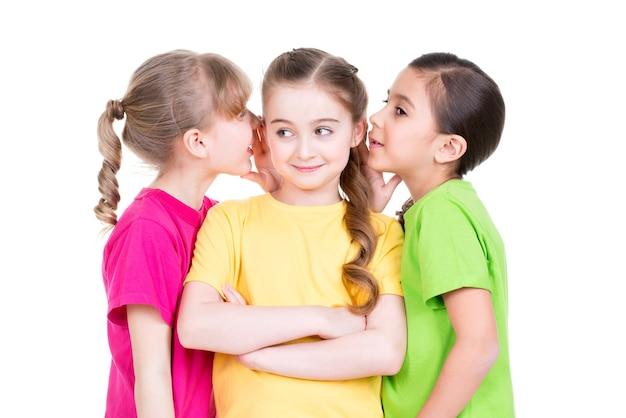 Drie klein schattig glimlachend meisje in kleurrijke t-shirts roddels - geïsoleerd op wit.