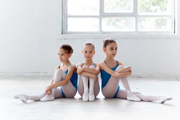 Drie kleine en balletmeisjes die samen zitten stellen