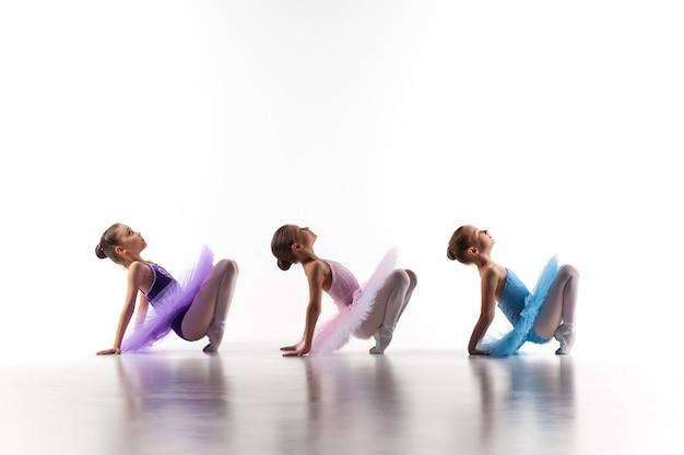 Drie kleine in tutu zitten en balletmeisjes die samen stellen