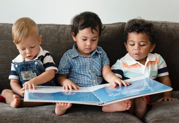 Drie kleine jongens die een boek op een bank lezen