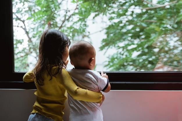 Drie kleine kinderen zien uit het raam