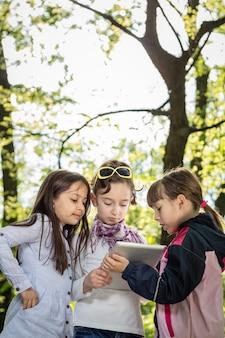 Drie kleine meisjes buiten werken op tablet
