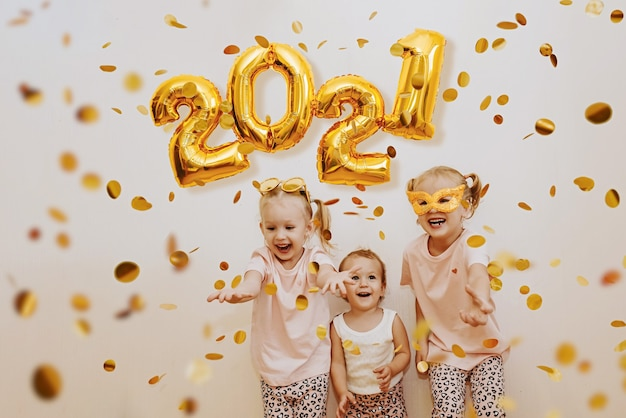 Drie kleine meisjes genieten van de vliegende gouden confetti