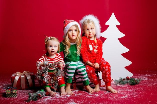Drie kleine meisjes in petten zitten naast een decoratieve witte kerstboom met n cadeautjes