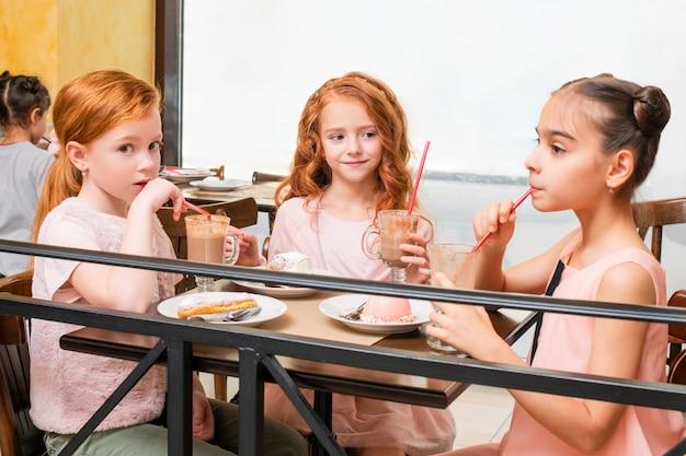 Drie kleine meisjes zitten aan een tafel in een café, drinken vrolijk warme chocolademelk en eten taarten