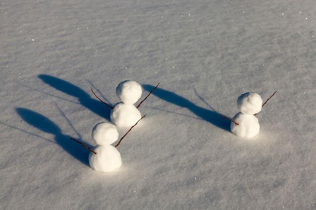 Drie kleine sneeuwpoppen in het winterseizoen, de sneeuwpop is gemaakt van verschillende onderdelen en staat in de sneeuw bij koud weer, spelletjes in de sneeuw met het maken van verschillende sneeuwpopfiguren
