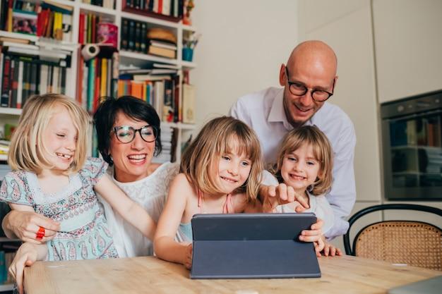 Drie kleine zusjes binnenshuis thuis met behulp van tablet zittafel onder toezicht van ouders