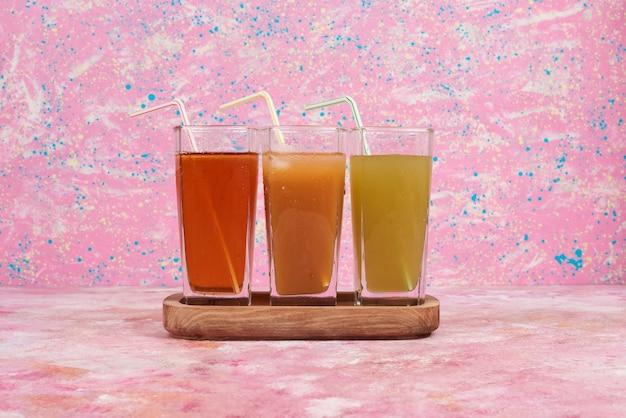 Drie kleurenglazen sap in een houten plank.