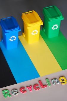 Drie kleurgecodeerde prullenbakken, isometrische afbeelding op geometrische papier achtergrond met kopie-ruimte.