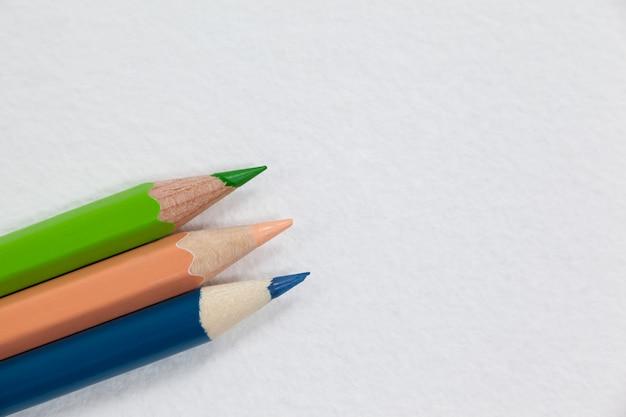 Drie kleurpotloden op witte achtergrond
