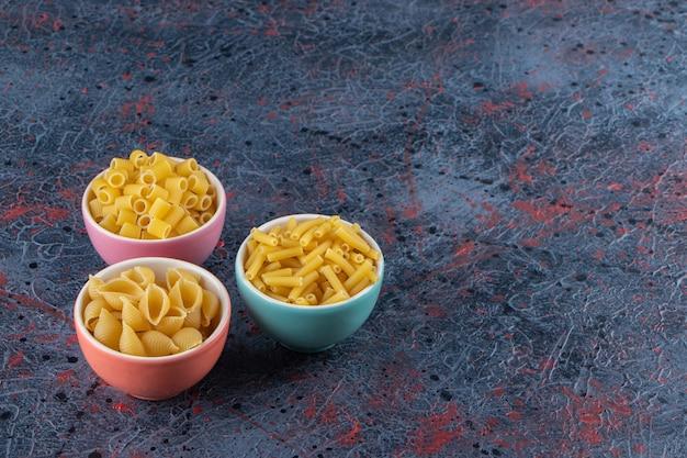 Drie kleurrijke borden met verschillende soorten ongekookte pasta op een donkere achtergrond.