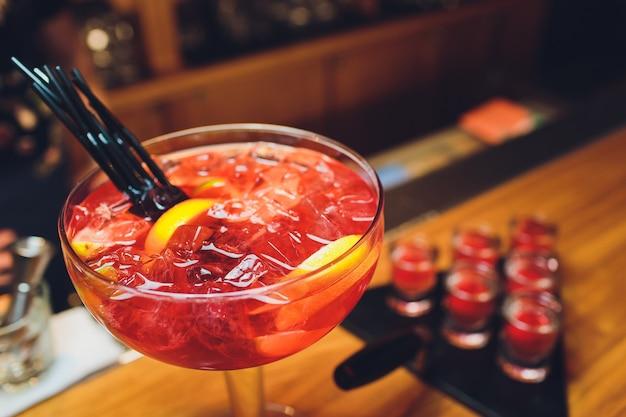 Drie kleurrijke cocktails in grote glazen in een klassieke baromgeving met tientallen wazige drankflessen op de achtergrond.