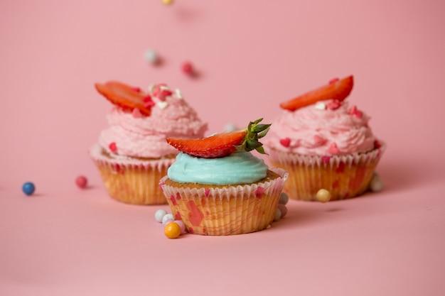 Drie kleurrijke cupcakes met aardbeien op roze achtergrond met kleurrijke snoepjes