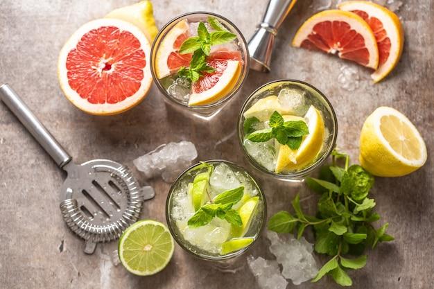 Drie kleurrijke gin tonic cocktails in whiskyglazen op toog in pup of restaurant - bovenaanzicht.