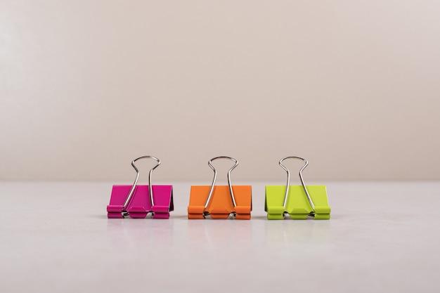 Drie kleurrijke paperclips op witte achtergrond