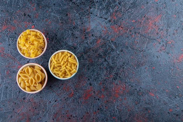 Drie kleurrijke platen met verschillende soorten ongekookte pasta op een donkere achtergrond.