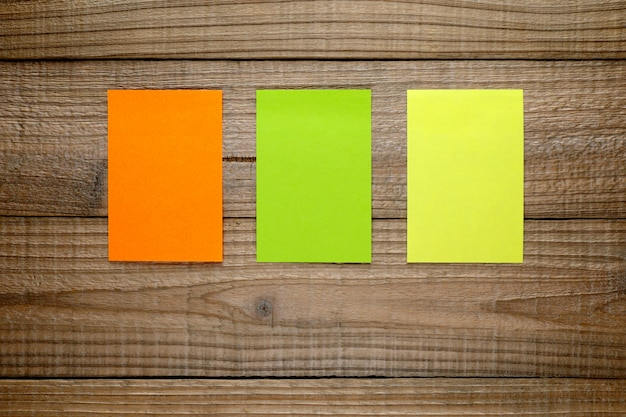 Drie kleurrijke post-itnota's op hout