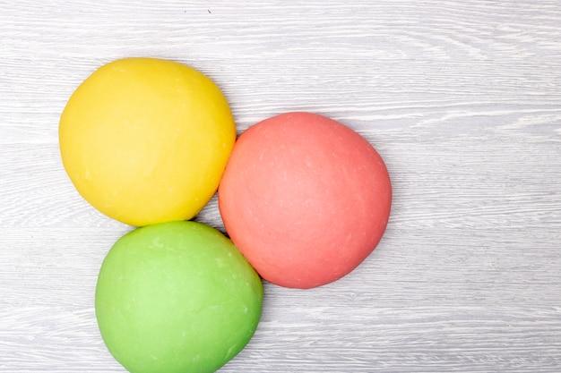 Drie kleurrijke rode, groene en gele deeg op tafel