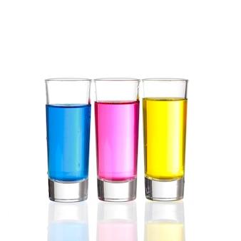 Drie kleurrijke shot dranken op een witte achtergrond met reflecties