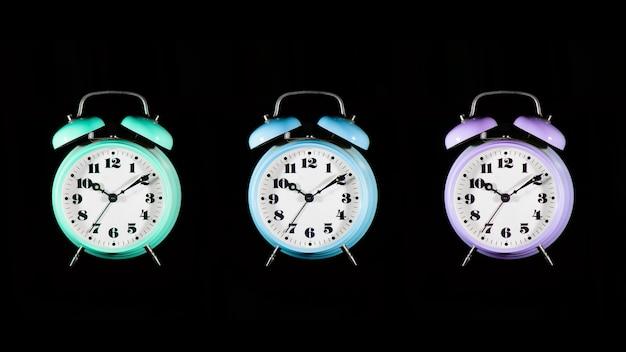 Drie kleurrijke wekkers op een zwarte achtergrond