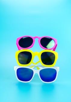 Drie kleurrijke zonnebril bij lichtblauwe studioachtergrond
