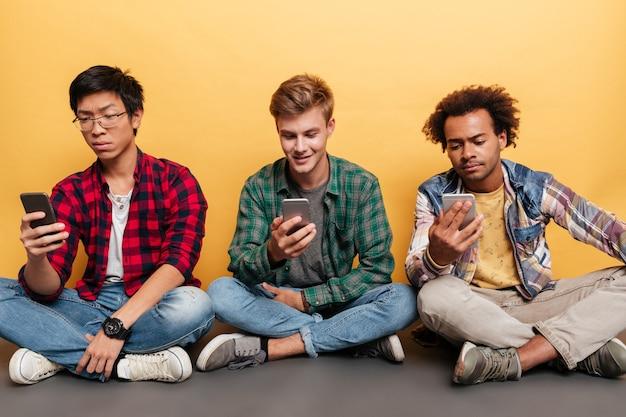 Drie knappe jonge mannen vrienden met behulp van mobiele telefoon over gele achtergrond