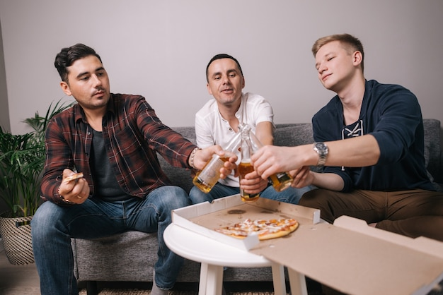 Drie knappe jonge vrienden die pizza eten en het van tafel halen