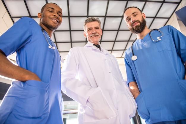 Drie knappe mannelijke artsen die camera in het ziekenhuis bekijken.