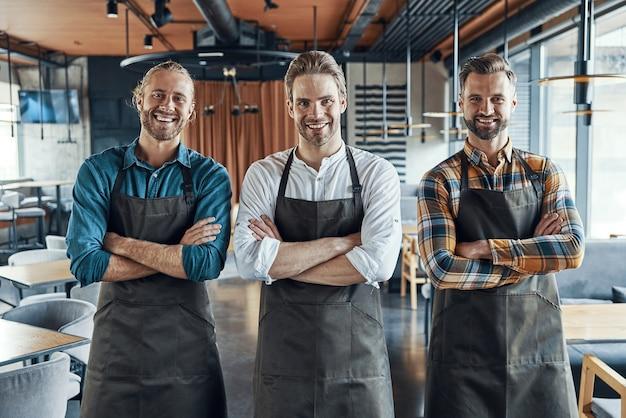 Drie knappe mannelijke obers in schorten die de armen gekruist houden en