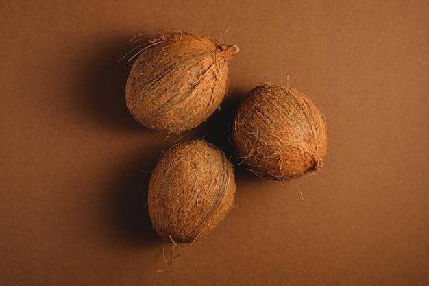 Drie kokosvruchten op trillende bruine duidelijke achtergrond, tropisch concept, hoogste mening