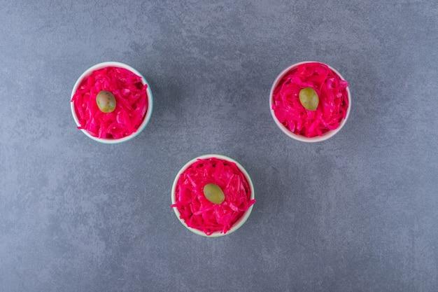 Drie kom vol met roze zuurkool over grijs.