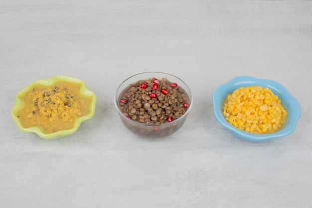 Drie kommen gekookte maïs, soep en bonen op een witte ondergrond.