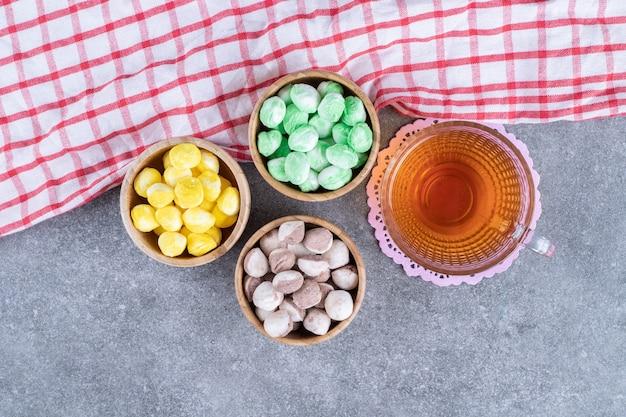 Drie kommen kleurrijke snoepjes met hete thee op marmeren oppervlak