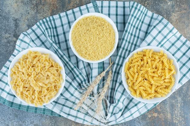 Drie kommen pasta naast twee tarwe op de handdoek, op het marmeren oppervlak.