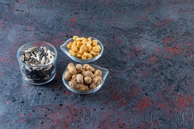 Drie kommen pinda's, zonnebloempitten en crackers op blauwe achtergrond.