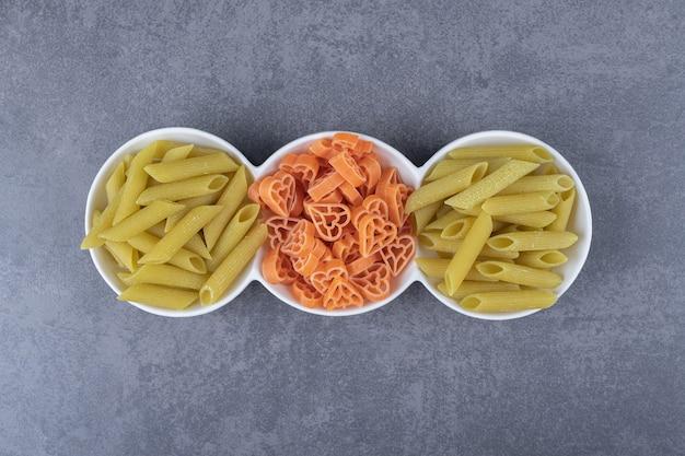 Drie kommen van verschillende pasta op stenen achtergrond.