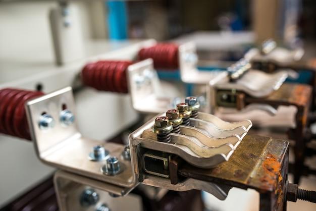 Drie koperen hoogspanningsklemmen met keramische cilinders en aangesloten hoogspanningsgeleider in testopstelling