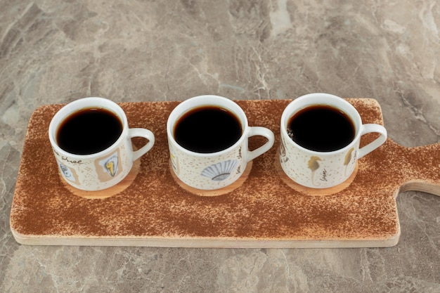 Drie kopjes espresso op een houten bord