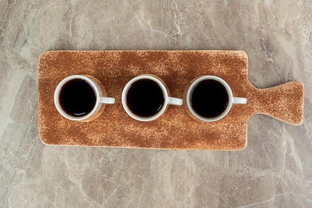 Drie kopjes espresso op houten plank