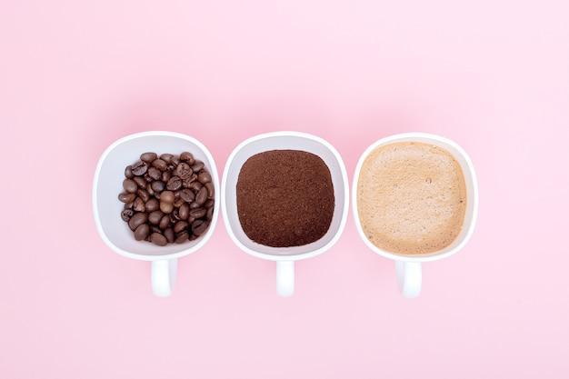 Drie kopjes verschil stadia van koffiebereiding of het maken van koffiedrank geïsoleerd op roze achtergrond, kopieer ruimte. bovenaanzicht.